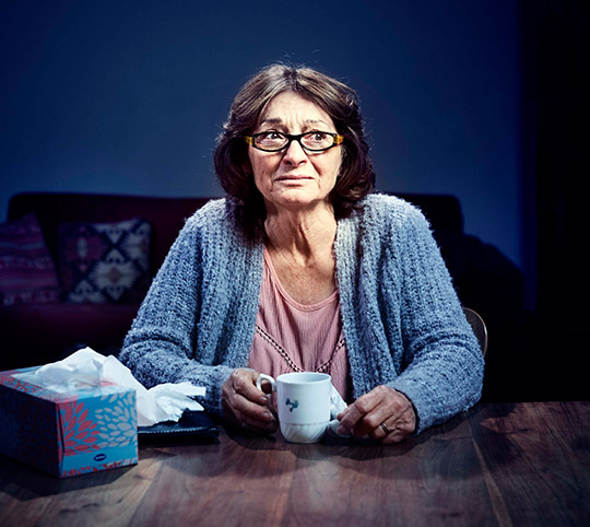 Woman in her 50s sitting at a table with a box of tissues and holding a mug of tea.