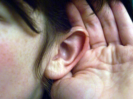 person holding hand behind ear, straining to hear